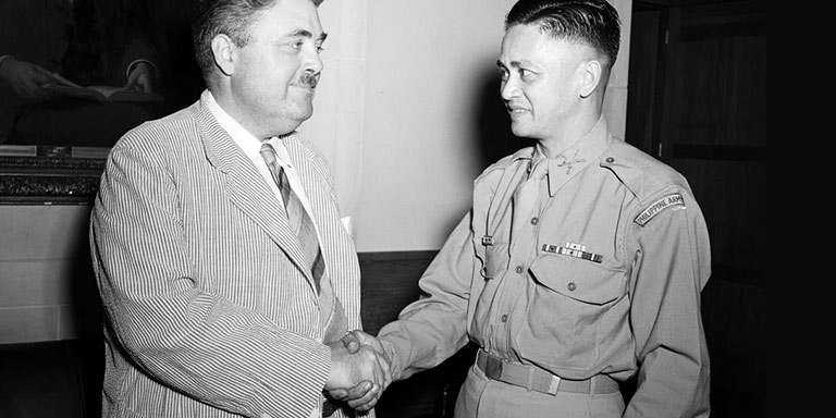 Archival photo of Herman B Wells shaking hands with a Philippine soldier
