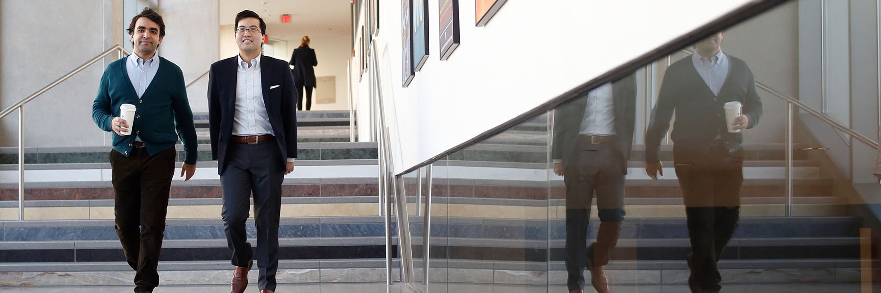 Two people walking down the stairs at SGIS.